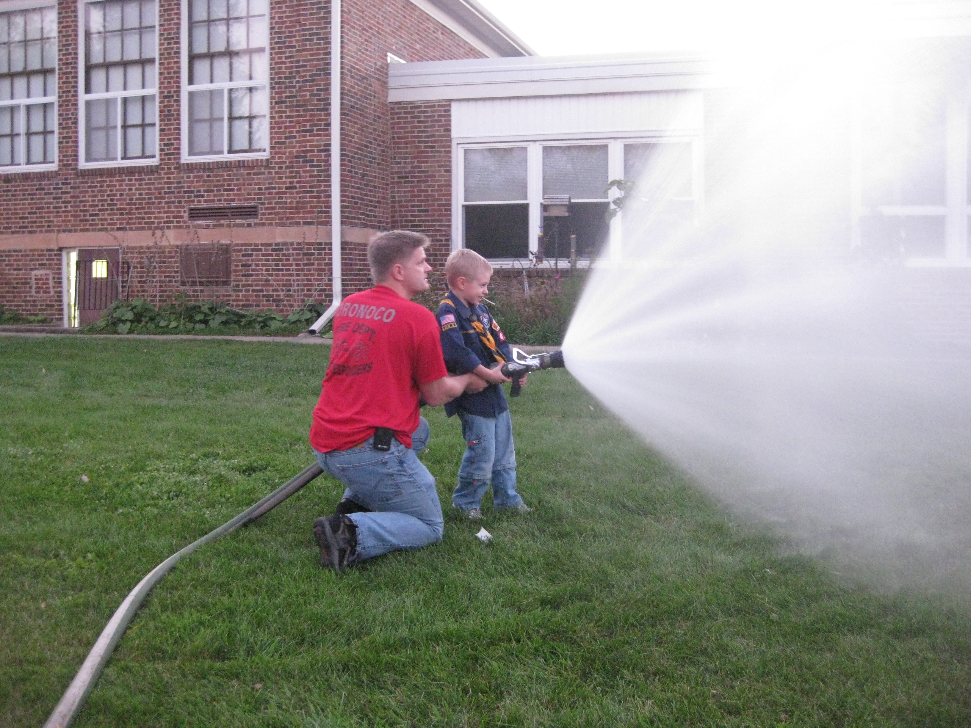 Ethan spraying water hose s cub scout popcorn